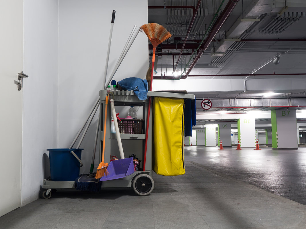 Cleaning large business with janitorial cart.